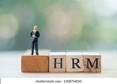Miniature businessman standing on wooden block word HRM in concept of human resource management concepts. (Human resource management : HRM)