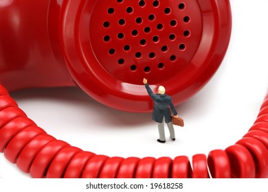 Miniature businessman stands in front of a red telephone receiver waving for help. He feels small and helpless. IT support or customer service concept.