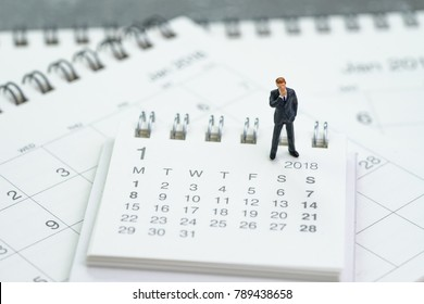 Miniature businessman thinking and standing on calendars using as business goals or future thinking.
