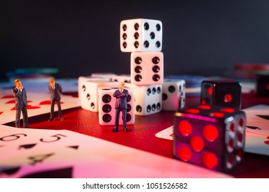 Miniature businessmen figurines making a deal on casino gambling card game table