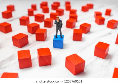 Miniature businessmen surrounded by wooden blocks representing possible choices and solutions to problem