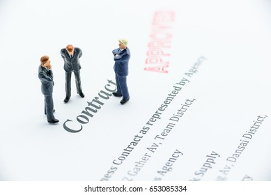 Miniature businessmen wear business attire stand and discuss about company contract. A contract is a voluntary arrangement between two parties that is enforceable by law as a binding legal agreement.