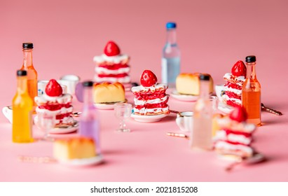 Miniature cakes and drink on pink background