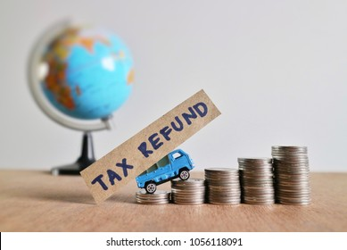 """Miniature car carry paper with """"tax refund"""" word and drives on roll increasing ladder of coin money on wood table in blur world globe on white background"""
