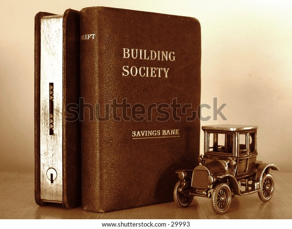 Miniature car standing beside two money boxes in the form of books.  Represents concept of 'Saving for the real thing'