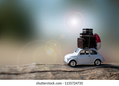 Miniature car with suitcases and summer background