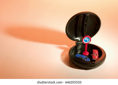Miniature Cars in Compact Case on Warm Background