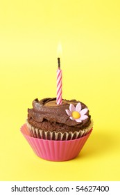 Miniature chocolate cupcake with icing, decorative flower and birthday candle on yellow background