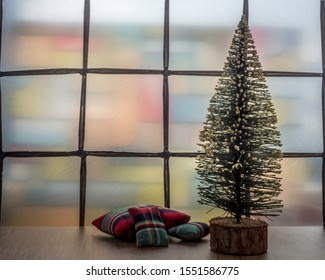 Miniature Christmas tree with cushions on a wooden floor. Window with stained glass. Room for copy.