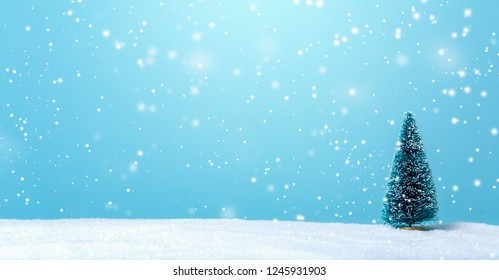 Miniature Christmas tree in a snow covered landscape