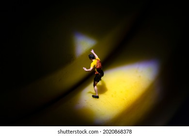 Miniature climber on banana in dark
