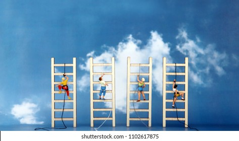 Miniature climbers climbing a wooden ladder against the backdrop of the blue sky. Competitive social concept.