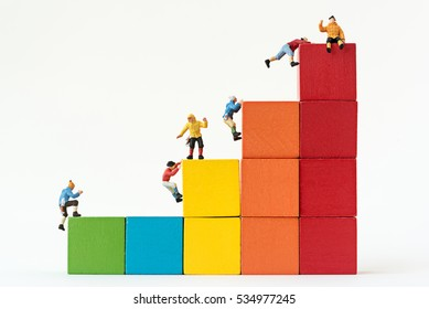 Miniature climbers team climbing on stack of cube building blocks
