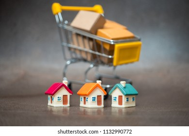 Miniature colorful house on mini shopping cart background using as property, e-commerce and business concept