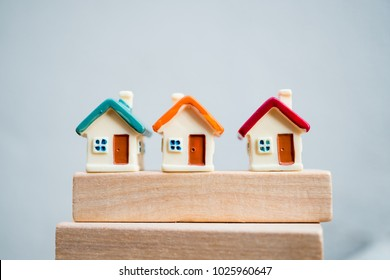 Miniature colorful house on wooden background using as property and financial concept
