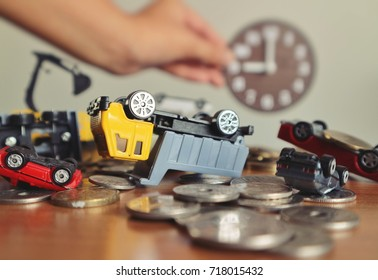 Miniature construction truck and cars overturn upside down on pile of gold coins money on wood table and blur hand hold wooden clock in light yellow tone color