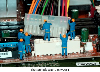 Miniature construction worker figurines posed as if working on a computer motherboard.
