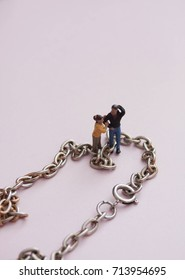Miniature couple chained together. Concept of marriage or divorce,