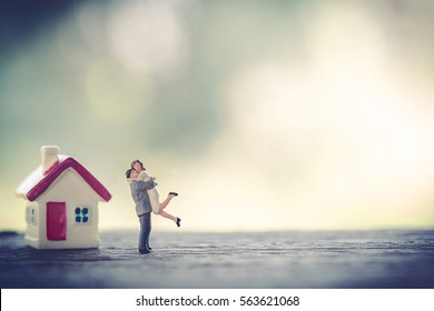 miniature couple and miniature house with red roof on wooden mock up over blurred green garden on day noon light.Image for property real estate investment concept.  Image for Love couple concept.