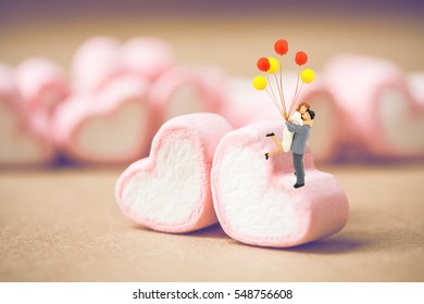miniature couple with red and yellow balloon on marshmallow , Image for Love couple and Happy valentine day concept.