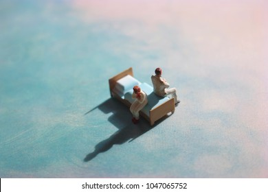 Miniature couple sitting on a bed. Dreamy, cloud-like background. Couple in conflict in the bedroom.
