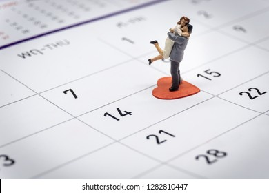 miniature couple standing on Calendar. Day 14 meets Valentine Day.