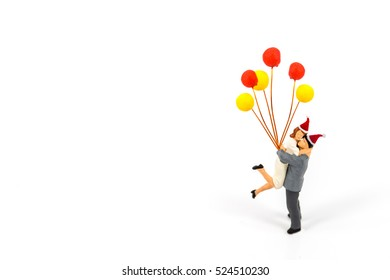 miniature couple wear Christmas hats with balloon isolated on white, Image for Love, couple concept
