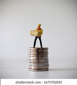 A miniature courier standing on a pile of coins.