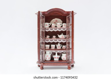 Miniature cupboard with faience dishes from a dollhouse isolated