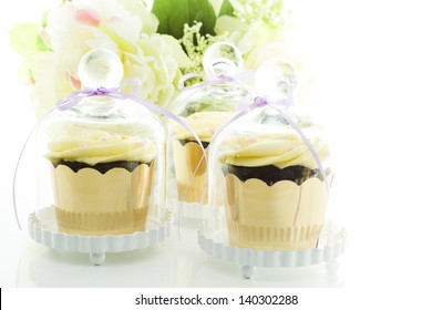 Miniature cupcakes in individual glass stands.