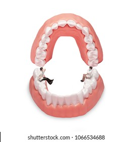 """Miniature dentist and nurse """"team specialists"""" observing and discussing about human teeth with gums and enamel"""