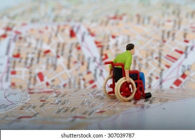 Miniature of a disabled man on a wheelchair across a city map