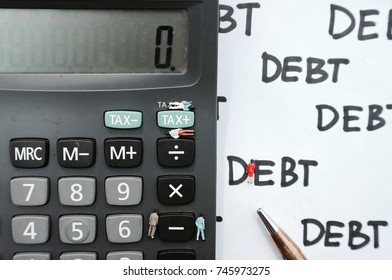 Miniature dolls on calculator near tax word and minus symbol, tiny figurine and pen on debt written on white paper
