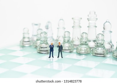 Miniature dolls on the chess board.