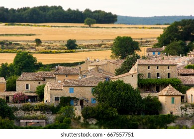 Miniature effect of small provence village on hill in countryside and wheat fields in golden sunset – trip to France