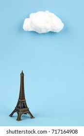 miniature eiffel tower and cumulus on sky blue background
