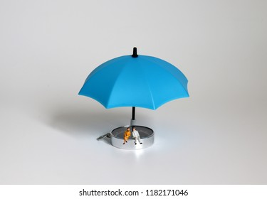 The miniature elderly couple sitting on the compass and the blue umbrella.