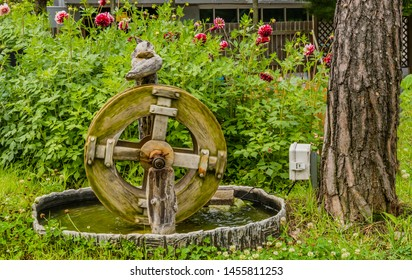 Miniature electric waterwheel in front of green bushes with red flowers. Wheel blurred for effect using slow shutter speed.
