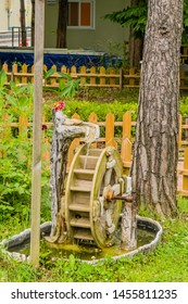 Miniature electric waterwheel in garden in front of tree and picket fence. Wheel blurred for effect using slow shutter speed.