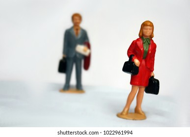 Miniature elegant woman and some man behind her, looking or follow the lady, stalking or sexual harassment concept, admirer, tension in relationship.