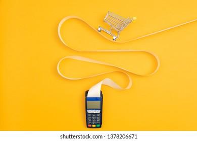 Miniature empty shopping cart on a long POS terminal receipt, expensive shopping concept