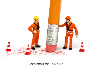 Miniature engineer or technician holds a pencil and erases a mistake while his associate watches. Engineering, construction, or technical mistake concept.