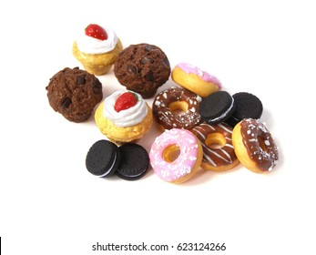 Miniature fake cakes and donuts on white background. Dollhouse miniature, polymer clay toy, plastic dummies