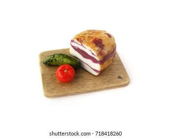 Miniature fake Ukrainian bacon on tray with salted tomato and cucumber on white background. Dollhouse miniature, polymer clay toy, plastic dummies