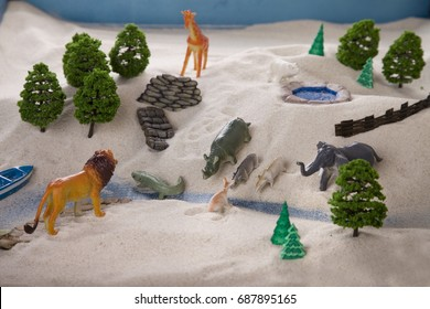 Miniature family constellations, toy zoo. Sand therapy. The child is built in a sandbox world, the animals came to drink. The work of the psychologist. Psychotherapy session. Lion, Rhino, elephant