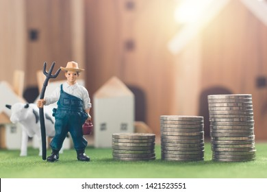 Miniature Farmer and cow figure model with money coin stack on Simulation grass, Wooden house in the background, agriculture and financial concept