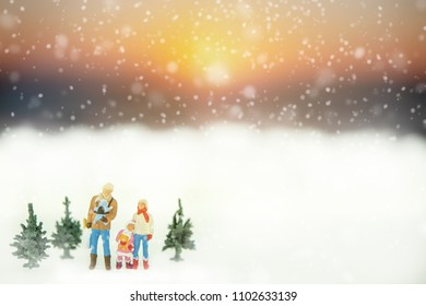 Miniature of father and mother with her daughter on sunset background in snowing day.