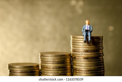 miniature figure business man sitting on top of pile stack of golden coins. business success concept
