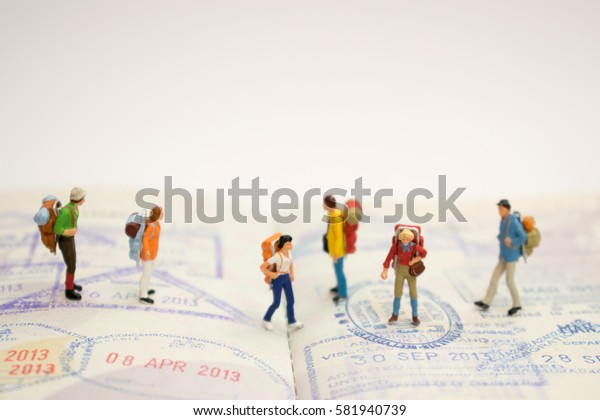 Miniature figure : Close up of group of younger traveler standing on visa stamps , backpack and travel concept.