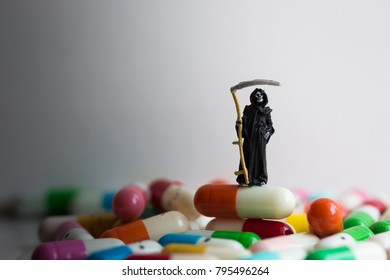 Miniature figure : The grim reaper of death stands on medicinal capsules. Image use for Misuse of drugs, Read labels before using the drug.